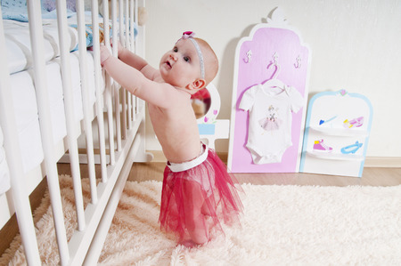 Little baby girl ( 7 mounth old ) standing at childrens room near the bed