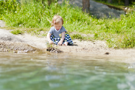 Little girl playing on the river bank