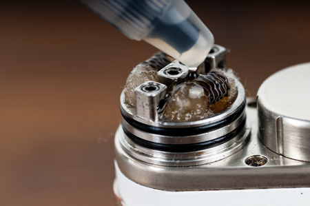 e cig: Applying liquid with nicotine in the coils on the RDA Stock Photo