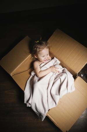 Niña que se sienta en una caja