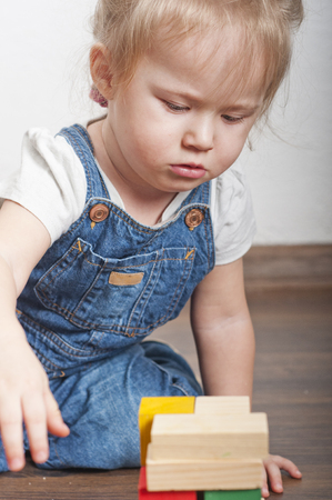 Little cute girl playing with a wooden constructor