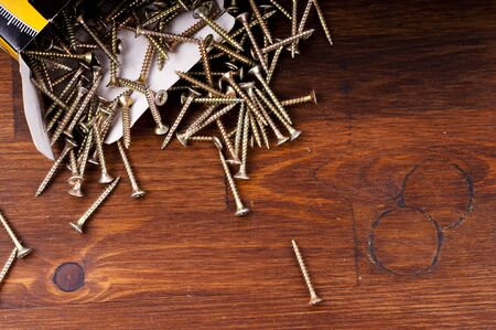 plating: Yellow passivated screws on wood desk Stock Photo