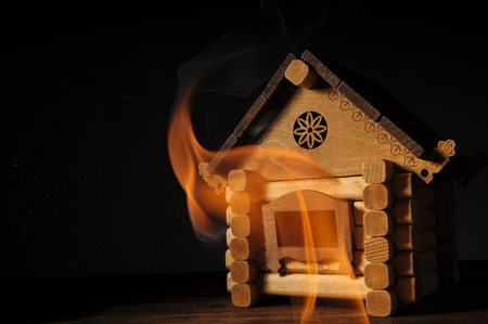 The concept of fire. Wooden house on fire