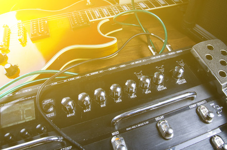 Guitar & digital guitar effects processor lying on the stage in the spotlight