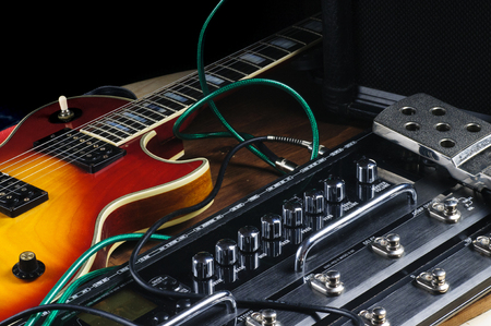 Guitar and stompbox laying there on the stage Stock Photo