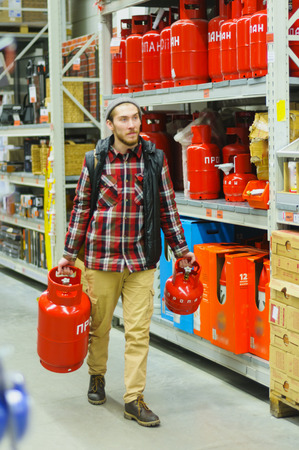 EKATERINBURG, RUSSIA - JANUARY, 8, 2018: A young man chooses gas cylinder in the hardware store