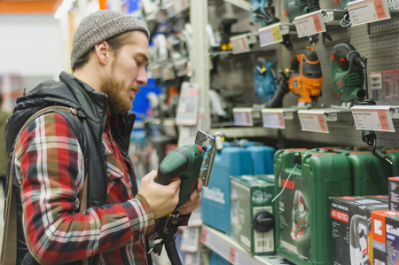 EKATERINBURG, RUSSIA - JANUARY, 8, 2018: A young man chooses electric jig saw in the hardware store