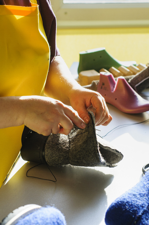 Handmade shoes. The process of making fashionable and stylish shoes from natural felted wool. Stock Photo
