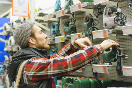 Man chooses an electric jigsaw in a  hardware store Stock Photo