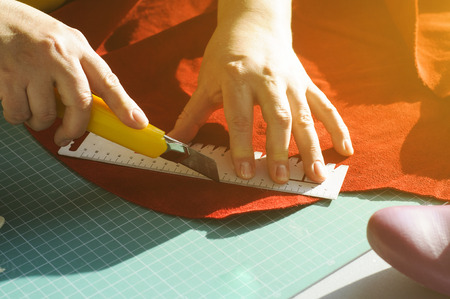 Hands of the master. Marking and slicing red leather for making bags, purses or shoes.