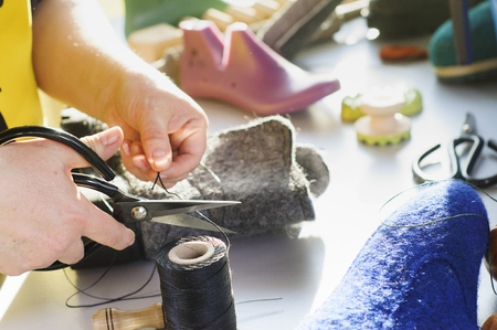 The master makes warm boots from natural felted wool. Handmade shoes. Stock Photo
