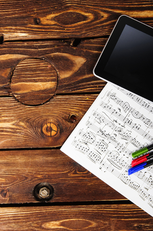 Sheet music and tablet on the table. Working place of the modern composer. Stockfoto