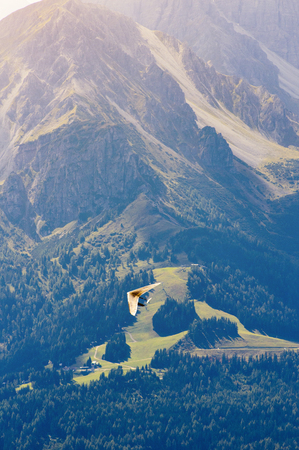 Extreme sport hang gliding. The glider flies among the mountain peaks in the rays of the bright sun in the Alps. Stockfoto