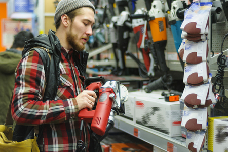 EKATERINBURG, RUSSIA - JANUARY, 8, 2018: A young man chooses channel cutter wall chaser with twin blade in the hardware store
