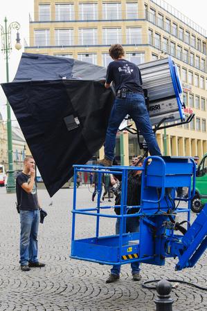 PRAGUE, CZECH REPUBLIC - SEPTEMBER, 13, 2014: The technician installs a huge softbox on a powerful spotlight. Shooting a movie or TV series. Redactioneel