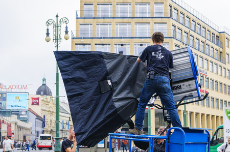 PRAGUE, CZECH REPUBLIC - SEPTEMBER, 13, 2014: The technician installs a huge softbox on a powerful spotlight. Shooting a movie or TV series. Editorial