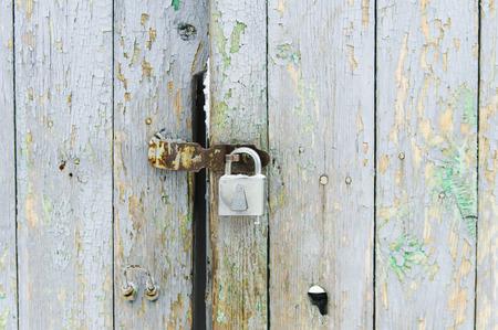 Padlock on the old door with peeling paint Standard-Bild