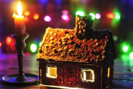 Gingerbread Christmas house and a candle on a bright background Archivio Fotografico