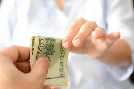 Give money to someone as bribe to suggest a corrupt system Stock Photo