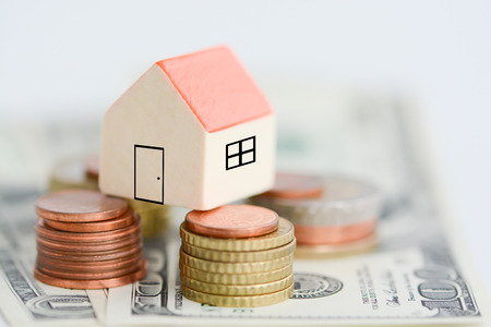 Model house on top of money pile suggesting savings for a house