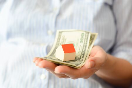 Woman holding a model house on top of money pile suggesting savings for a house Stock Photo