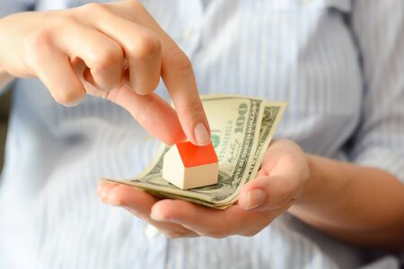 model house: Woman holding a model house on top of money pile suggesting savings for a house Stock Photo