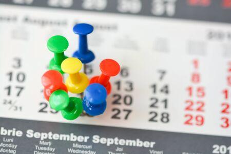 Varios pines en un calendario que sugieren un día ocupado o un horario Foto de archivo