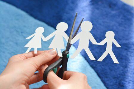 conflictos sociales: concepto de divorcio de la familia con las formas y las tijeras de papel humanos que sugieren problemas de relación