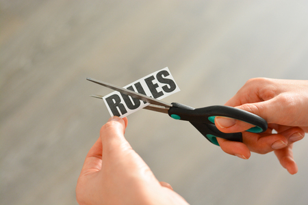 "Woman hands cutting with scissors a printout reading ""RULES"""