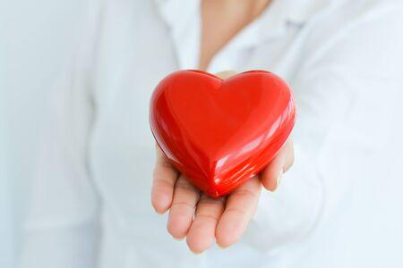 Vrouw die en een rode hartvorm houdt beschermt Stockfoto