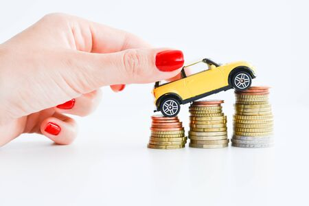 Woman hand pushing a toy car over a stack of coins