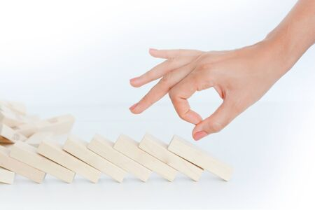 Human hand starting a domino effect concept with wooden blocks Stock Photo