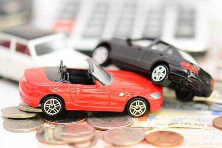 carritos de juguete: Concepto del seguro de coche con los coches de juguete colorido, llave del coche, monedas y billetes