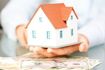 Woman hand holding house on top of money suggesting the rising cost of home prices