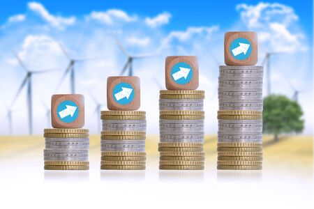 Wind energy industry growth with graph chart coin pile on windmills background Stock Photo