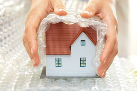 model house: Woman hands covering a model house with plastic wrapper house protection or insurance concept