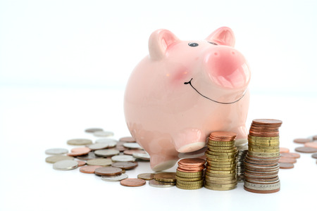 Piggy bank climbing on piles of money suggesting cash savings growth