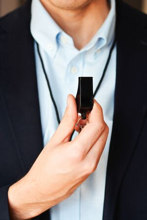 Businessman holding whistle suggesting leadership or coaching training Zdjęcie Seryjne
