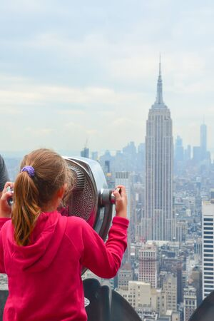 Little girl watching New York Empire State Building at city view point Publikacyjne