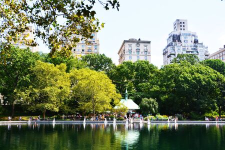 Summer day in Central Park, New York with toy boats on lake