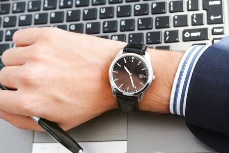Businessman hand looking at his watch suggesting being out of time Zdjęcie Seryjne
