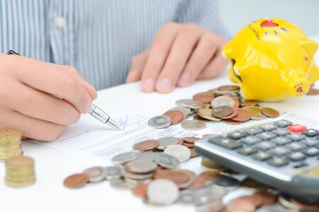 Tax calculation or new loan agreement with hand calculator and coins Zdjęcie Seryjne