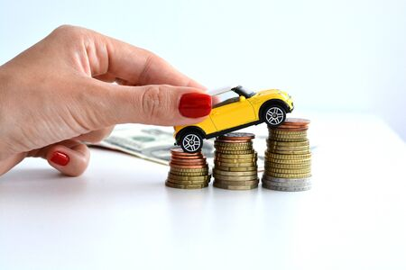 Business woman putting a yellow toy car on stack of coins suggesting automotive market increase Zdjęcie Seryjne