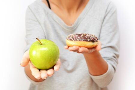 Healthy lifestyle or nutrition concept with young woman holding in hands an green apple and a donut Stock Photo