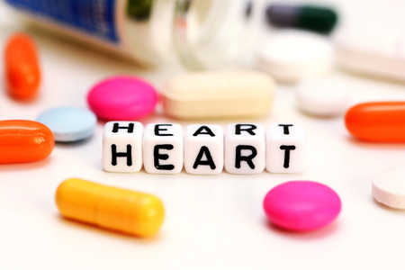 Multicolored medical drugs and letter cubes spelling heart, suggesting cardiac problems