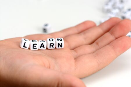 Close-up of child hand holding learn word from tiled letters