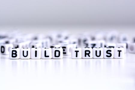 Bauen Sie Vertrauensverfahrenskonzept mit mit Ziegeln gedeckten Buchstaben auf weißem Hintergrund auf