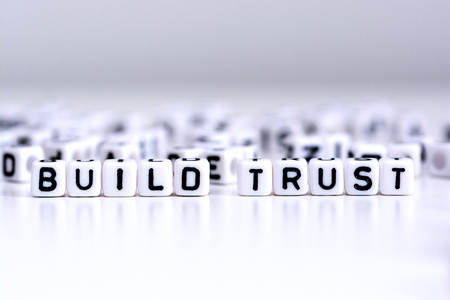 Build trust process concept with tiled letters on white background