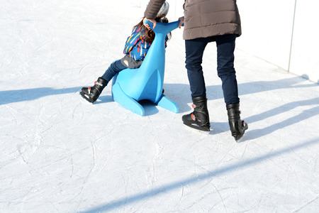 Family fun on outdoor ice rink, kid learning to skate with plastic seal as training aids