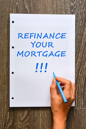 Woman hand writing refinance your mortgage on math book with marker